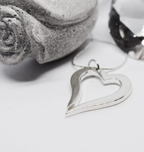 silverhjärta i kedja på vit bakgrund med grå ros i betong bredvid