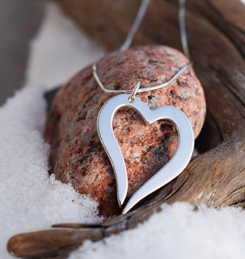 silverhjärta i kedja på röd sten med snö och trädgren utomhus