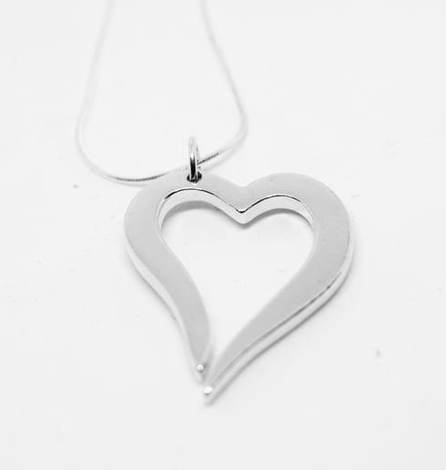 silverhjärta i kedja på vit bakgrund