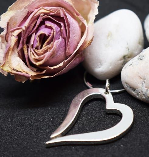 silverhjärta i kedja på svart bakgrund med stenar och ros i bakgrunden