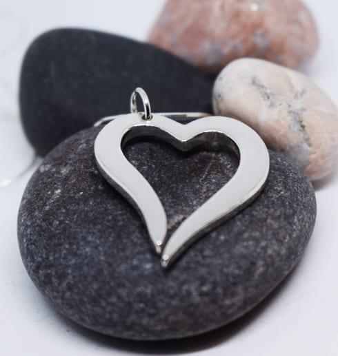 silverhjärta i kedja på grå sten med flera olika stenar bakom