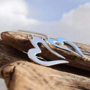 silverörhängen i form av hjärta på träbit utomhus