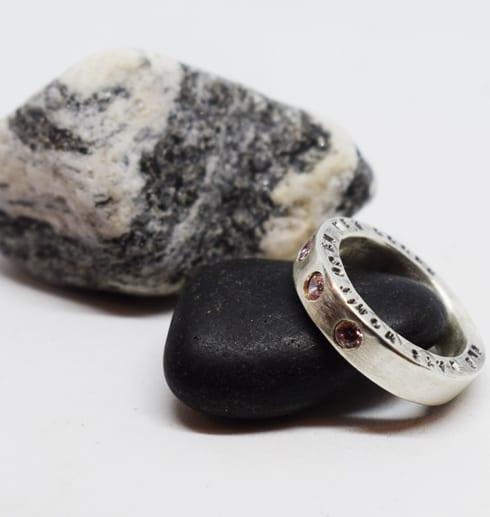 ring med stenar och text lutad mot svart sten med svartvit sten i bakgrunden
