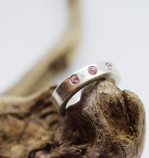 silverring med tre rosa stenar som ligger på en trädgren