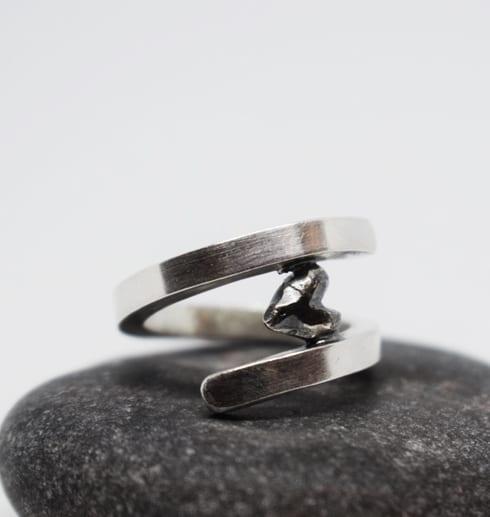 silverring med svart hjärta på grå sten