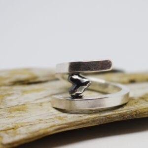 silverring med svart hjärta på träbit