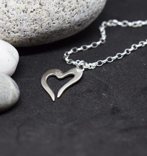 armband med litet silverhjärta på svart bakgrund med stenar bakom