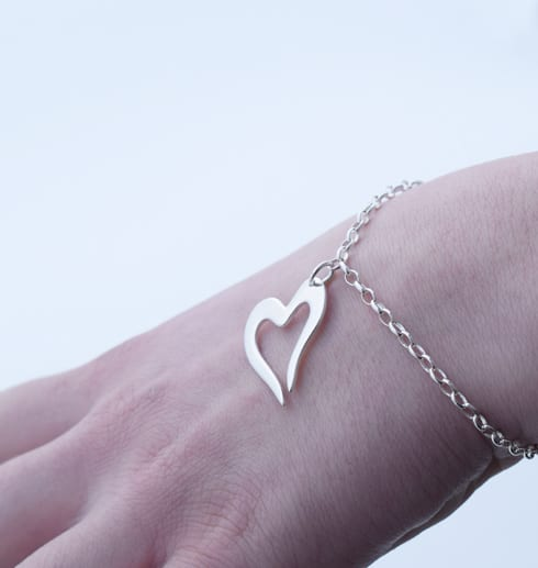 armband med litet silverhjärta på handled utomhus