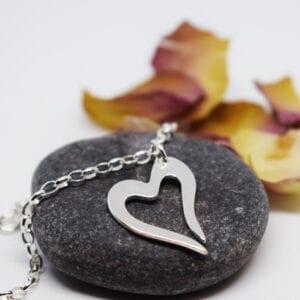 armband med litet silverhjärta på gråsten med rosenblad bakom