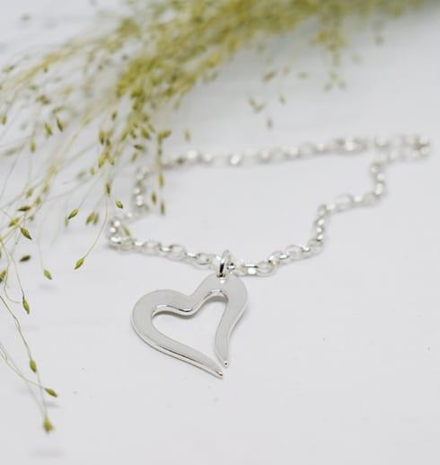 armband med litet silverhjärta på vit bakgrund med gulgrön kvist bredvid
