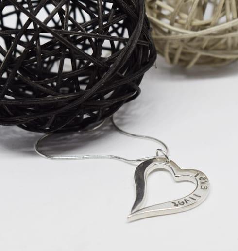 Silverhjärta i kedja på vit bakgrund med trådbollar bakom