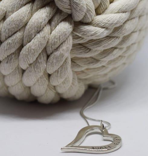 Silverhjärta i kedja på vit bakgrund med repboll bakom