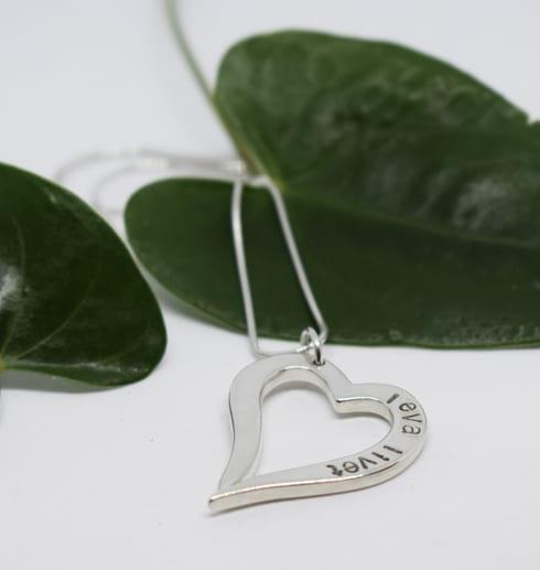 Silverhjärta i kedja på vit bakgrund med gröna blad bakom