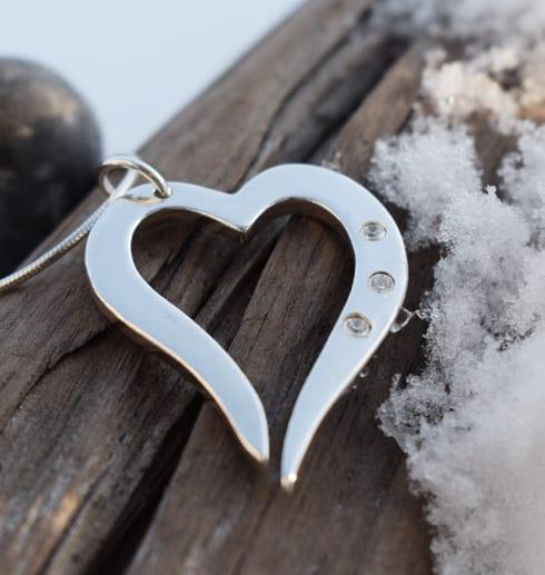 silverhjärta i kedja med tre gnistrande stenar på trädgren med snö utomhus