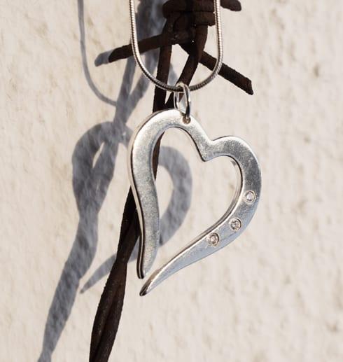 silverhjärta i kedja med tre gnistrande stenar på taggtrådshjärta utomhus