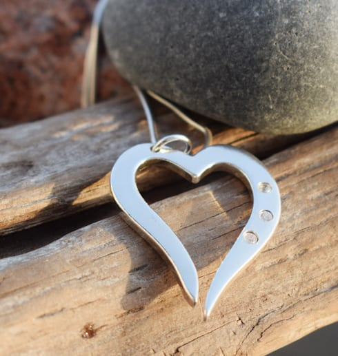 silverhjärta i kedja med tre gnistrande stenar på trädgren utomhus