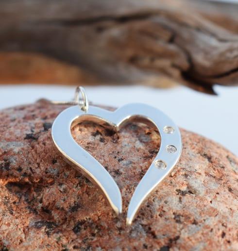 silverhjärta i kedja med tre gnistrande stenar på röd sten utomhus