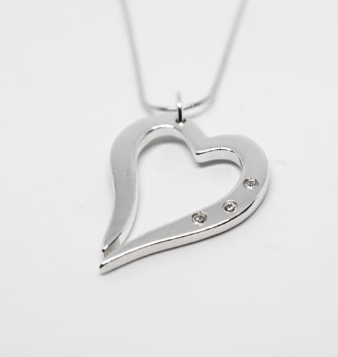silverhjärta i kedja med tre gnistrande stenar på vit bakgrund