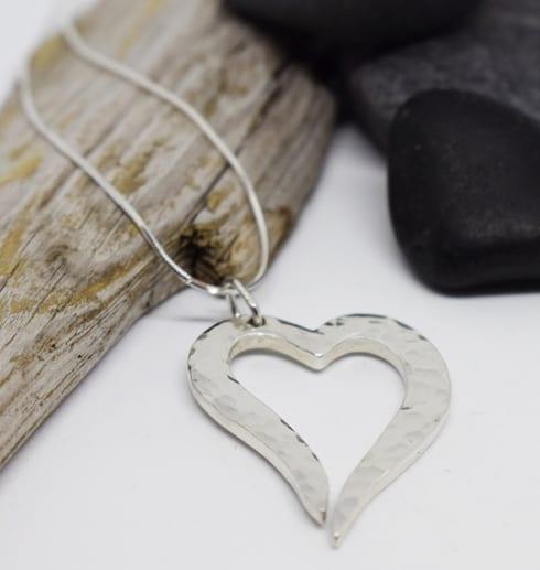 hamrat silverhjärta i kedja på vit bakgrund med stenar och träbit bredvid