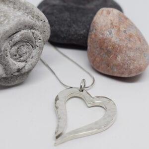 hamrat silverhjärta i kedja på vit bakgrund med stenar och en grå ros i betong bakom