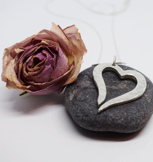 hamrat silverhjärta på grå sten med ros bredvid
