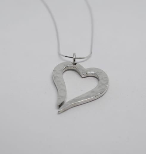hamrat silverhjärta i kedja på vit bakgrund