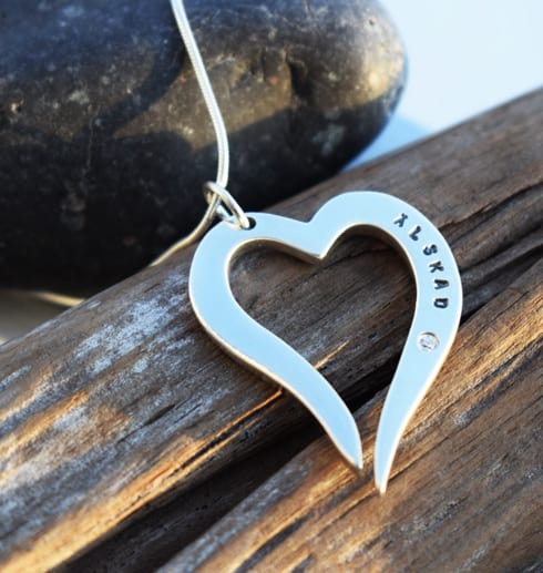 silverhjärta i kedja på trädgren med stena bakom utomhus