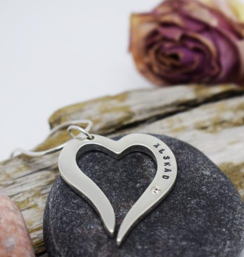 silverhjärta i kedja på grå sten med trädgren och ros bakom