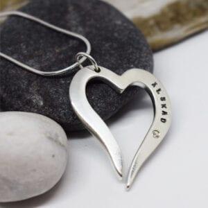 silverhjärta i kedja med grå och vit sten bakom