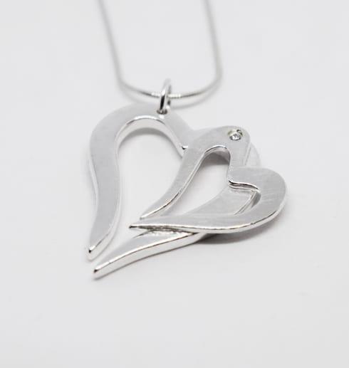 dubbelhjärta i silver som hänger i en kedja på vit bakgrund