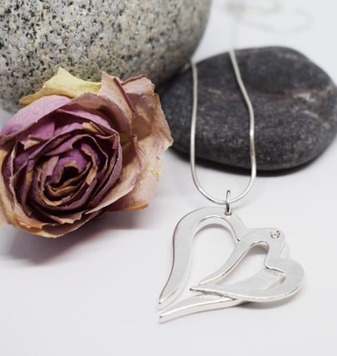 dubbelhjärta i silver som hänger i en kedja med stenar och ros bakom