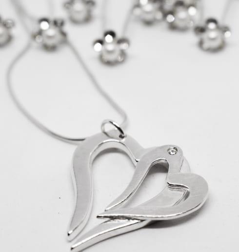 dubbelhjärta i silver som hänger i en kedja med glittriga hårnålar bakom