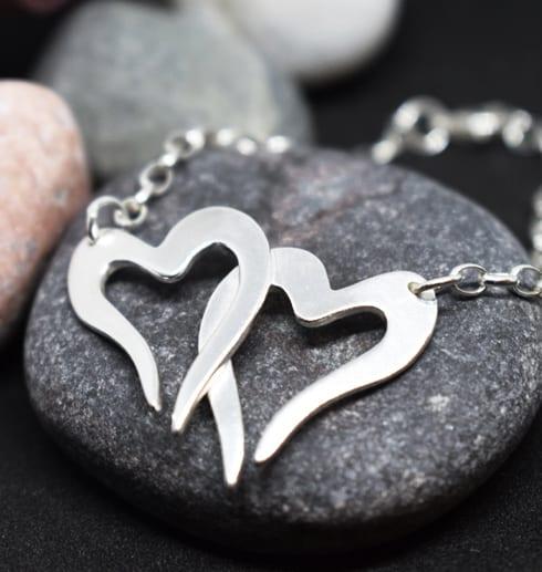 två hjärtan i kedja som armband på grå sten