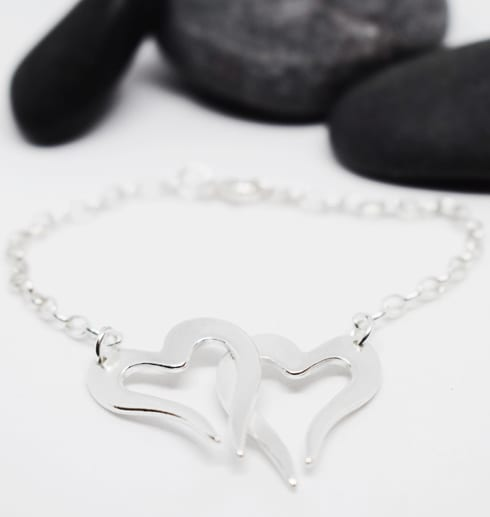 två hjärtan i kedja som armband på vit bakgrund med stenar bakom