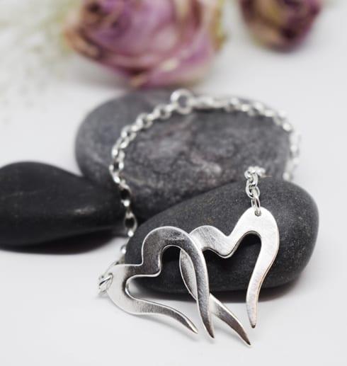 två hjärtan i kedja som armband på grå sten med rosor bakom
