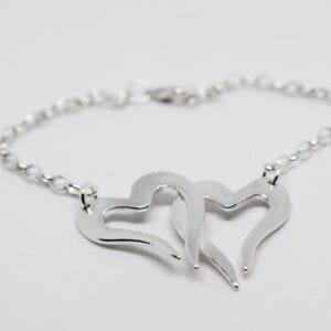 två hjärtan i kedja som armband på vit bakgrund