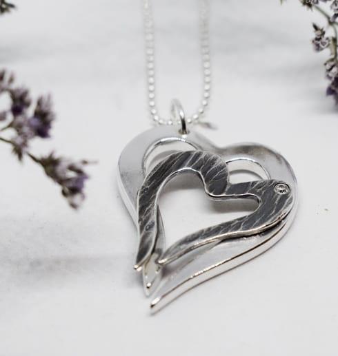 dubbelhjärta i silver på vit botten med blomma i en sidan