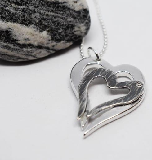dubbelhjärta i silver på vit botten med spräcklig sten i ena hörnet