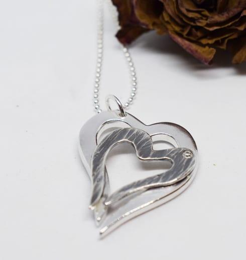 silverhjärtan på vit bakgrund med ros i ena hörnet