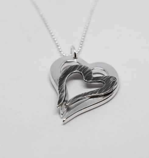 halsband i form av hjärtan i silverkedja på vit bakgrund