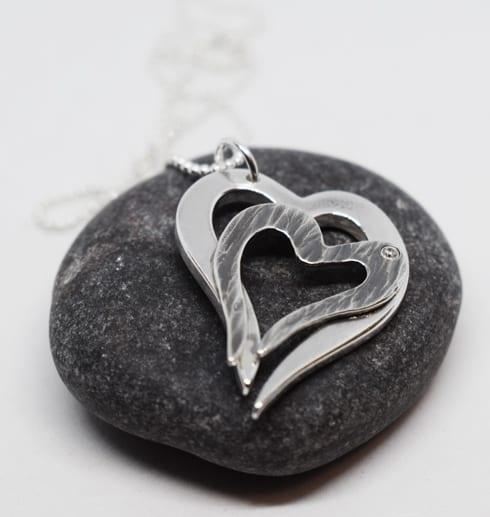dubbelhjärta i silver på grå sten
