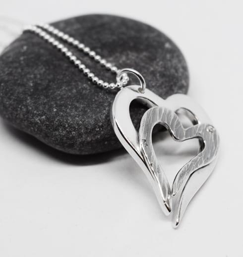 halsband i form av dubbelhjärta lutad mot dubbelhjärta