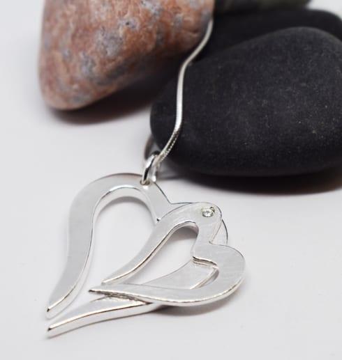 dubbelhjärta i silver som hänger i en kedja med stenar i bakgrunden