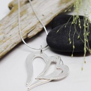 dubbelhjärta i silver som hänger i en kedja med stenar och träbit bakom