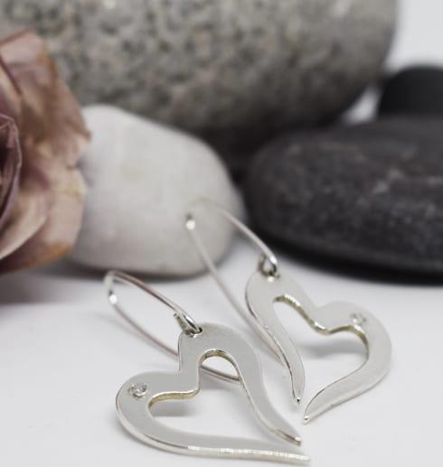 silverörhängen i form av hjärta på vit bakgrund med stenar och ros i bakgrunden