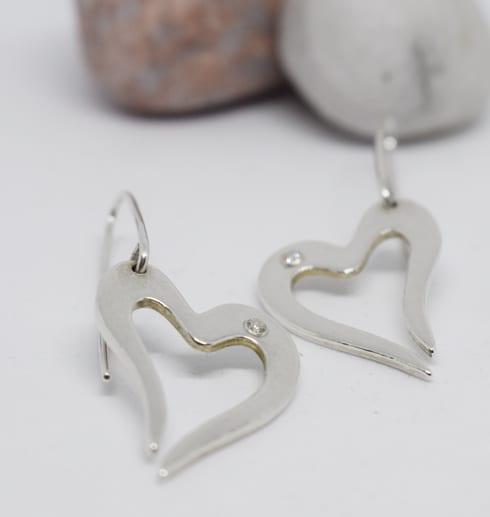 silverörhängen i form av hjärta på vit bakgrund med stenar i bakgrunden