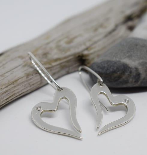 silverörhängen i form av hjärta på vit bakgrund med stenar och träbit i bakgrunden