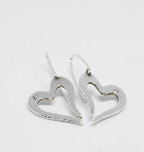 silverörhängen i form av hjärta på vit bakgrund
