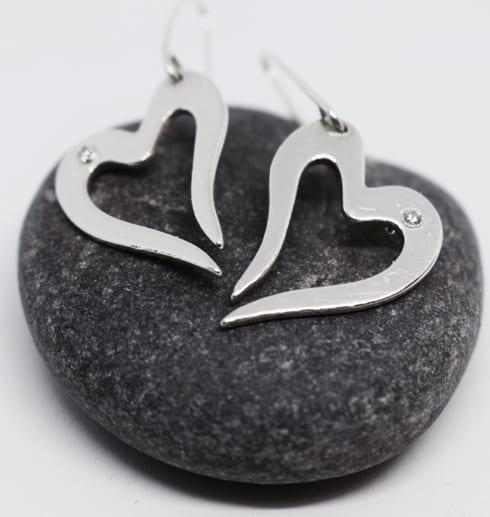 silverörhängen i form av hjärta på grå sten
