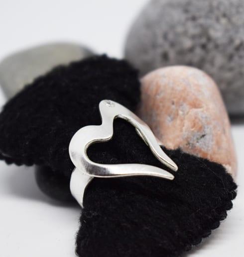 hjärtformad silverring på svart sammetshållare med stenar bakom